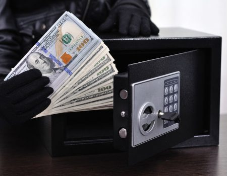 Thief steals dollars from the safe, close up
